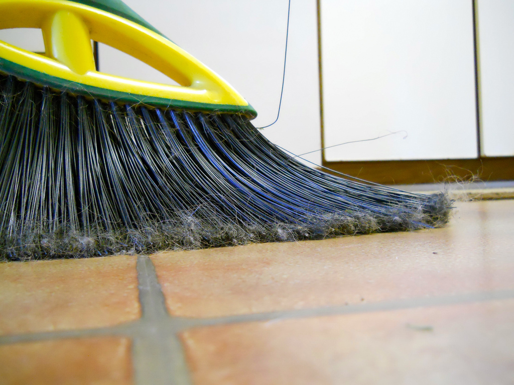 A broom sweeping a tile floor
